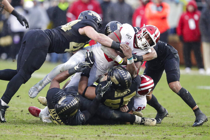 Indiana running back Sampson James (24) is tackled by Purdue cornerback Cam Allen (18) and linebacker Ben Holt (44) during the first half of an NCAA college football game in West Lafayette, Ind., Saturday, Nov. 30, 2019. (AP Photo/Michael Conroy)