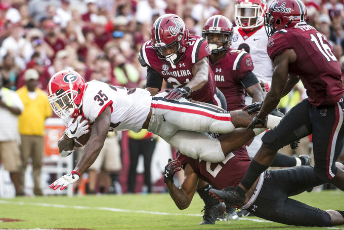 Georgia running back Brian Herrien (35) scores a touchdown against South Carolina defensive back Jamyest Williams (21) and Rashad Fenton (16) during the second half of an NCAA college football game Saturday, Sept. 8, 2018, in Columbia, S.C. Georgia defeated South Carolina 41-17. (AP Photo/Sean Rayford)