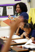 FILE - In this April 18, 2019 file photo, an anxious student raises her hand as Key Elementary School third grade teacher April Tate leads the class in a reading exercise, in Jackson, Miss. Nationally, lower-performing students are doing worse in math and reading, thus dragging down overall results on the Nation's Report Card. America's eighth graders are falling behind in math and reading, while fourth graders are doing slightly better in reading, according to the latest results from the Nation's Report Card. (AP Photo/Rogelio V. Solis, File)