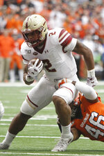 Boston's College's AJ Dillon, left, breaks a tackle by Syracuse's Lakiem Williams during the first quarter of an NCAA college football game in Syracuse, N.Y., Saturday, Nov. 2, 2019. (AP Photo/Nick Lisi)