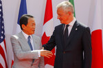 French Finance Minister Bruno Le Maire, right, welcomes Japan's Finance Minister Taro Aso at the G-7 Finance Wednesday July 17, 2019.The top finance officials of the Group of Seven rich democracies are arriving at Chantilly, at the start of a two-day meeting aimed at finding common ground on how to tax technology companies and on the risk from new digital currencies. (AP Photo/Michel Euler)