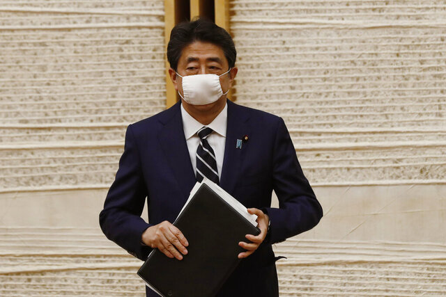 Japan's Prime Minister Shinzo Abe leaves a venue after a news conference in Tokyo Monday, May 25, 2020. Abe lifted a coronavirus state of emergency in Tokyo and four other remaining areas on Monday, ending the restrictions nationwide as businesses begin to reopen. (Kim Kyung-hoon/Pool Photo via AP)