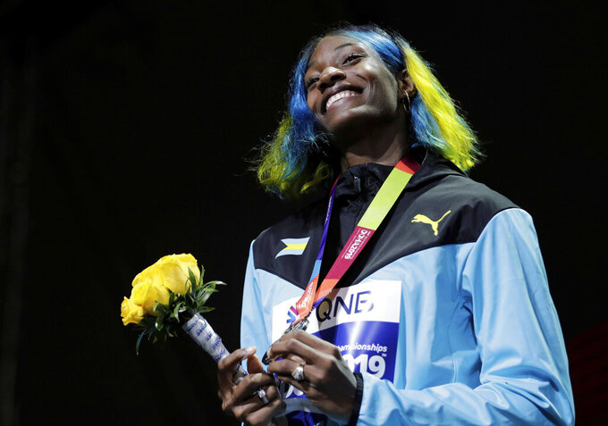 FILE - In this Oct. 4, 2019, file photo, Shaunae Miller-Uibo of Bahamas, silver, smiles during the medal ceremony for the women's 400-meter the World Athletics Championships in Doha, Qatar. Miller-Uibo won gold in Rio with a dive at the finish of the 400 meters. She's diving in at the Tokyo Games with plans to not only defend her title but chase after gold in the 200 meters. (AP Photo/Nariman El-Mofty, File)