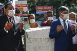 Colleagues of slain Saudi journalist Jamal Khashoggi, offer their prayers next to a monument, near the Saudi Arabia consulate in Istanbul, marking the two-year anniversary of his death, Friday, Oct. 2, 2020. The gathering was held outside the consulate building, starting at 1:14 p.m. (1014 GMT) marking the time Khashoggi walked into the building where he met his demise. (AP Photo/Emrah Gurel)