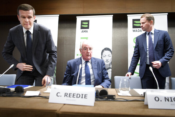 FILE - In this file photo dated Monday, Dec. 9, 2019, President-Elect of World Anti-Doping Agency (WADA) Witold Banka, left, President of World Anti-Doping Agency (WADA) Craig Reedie, center, and Director General of World Anti-Doping Agency (WADA) Olivier Niggli, right, arrive for a press conference after the WADA's extraordinary Executive Committee (ExCo) on the Russian doping data manipulation, in Lausanne, Switzerland. WADA announced a ban for Russia from international sporting events for four years. The Court of Arbitration for Sport judges will start on Monday Nov. 2, 2020, hearing four days of evidence and argument about allegations of a manipulated database from the Moscow testing laboratory. (Laurent Gillieron/Keystone FILE via AP)
