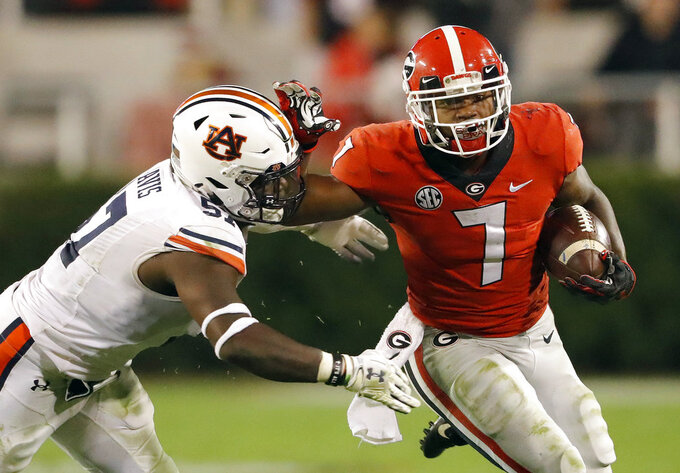 FILE - In this Nov. 10, 2018 file photo, Georgia running back D'Andre Swift (7) fends off Auburn linebacker Deshaun Davis (57) during the second half of an NCAA college football game in Athens, Ga. No. 1 Alabama's typically tough defense will be challenged by No. 4 Georgia's offense that enters Saturday's SEC championship game on a roll. (AP Photo/John Bazemore, File)