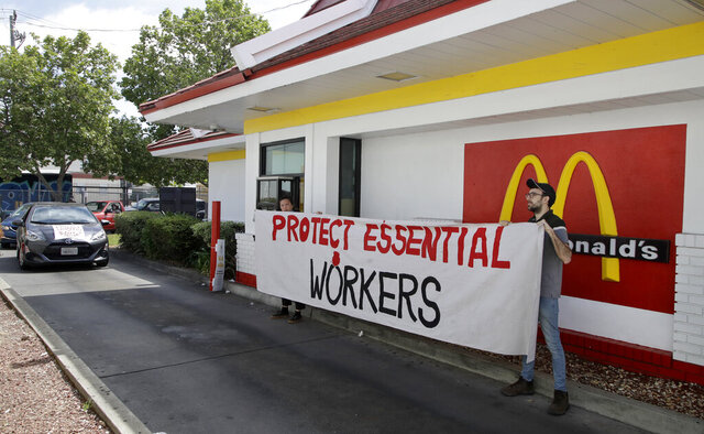 FILE - In this April 21, 2020, file photo, people protest what they say is a lack of personal protective equipment for employees as they close down the drive-thru at a McDonald's restaurant in Oakland, Calif. Across the country, the new, unexpected front-line workers of the pandemic — from grocery store and fast food workers to Instacart shoppers and Uber drivers — are taking action to protect themselves. (AP Photo/Ben Margot, File)