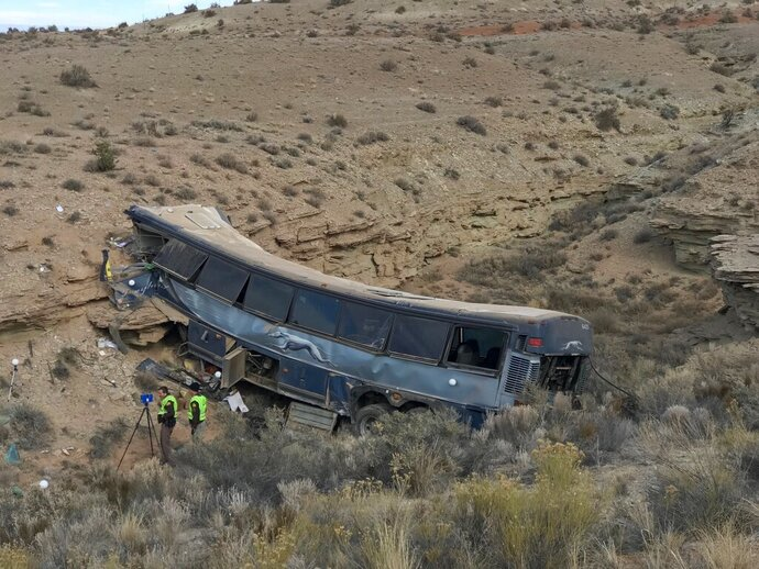 FILE - This Jan. 1, 2018, file photo, shows the aftermath of a Greyhound bus crash in Emery County, Utah. A man who suffered serious injuries when a Greyhound bus careened off a road in the Utah desert has sued the driver and the company, saying the driver was tired and sick and shouldn't have behind the wheel in a 2017 crash that killed one person and injured 12 others. Michael Edwards of Georgia says in the lawsuit filed Monday, May 13, 2019, in Nevada that Charles E. Saunders fell asleep after taking cold medicine and never hit the brakes as the bus flew off the highway and crashed into a canyon wall about 300 miles (483 kilometers) south of Salt Lake City. (Ben Tidswell/The Deseret News via AP, File)