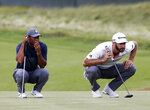 Tiger Woods, left, and Dustin Johnson line up their putts on the 16th green during the first round of the U.S. Open Golf Championship, Thursday, June 14, 2018, in Southampton, N.Y. (AP Photo/Seth Wenig)