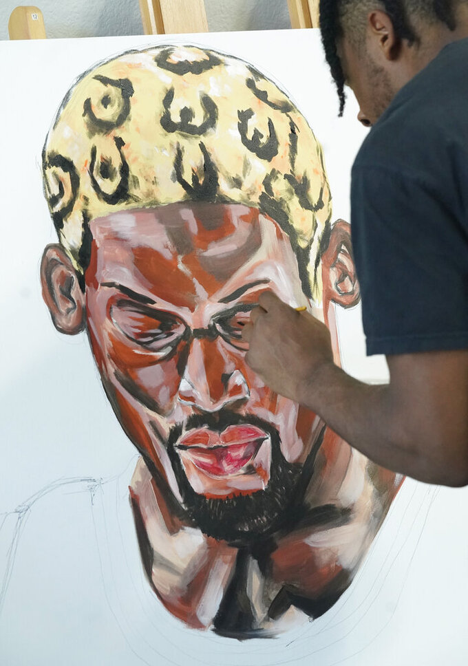 SMU defensive back RaSun Kazadi works on a painting at his apartment Wednesday, Aug. 11, 2021, in Dallas. The end of the NCAA ban on athletes being able to earn money for their fame and celebrity has led to some of them cashing in on their creative side. (AP Photo/LM Otero)