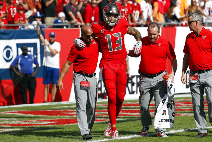 Tampa Bay Buccaneers wide receiver Mike Evans (13) is helped off the field after injuring his leg while scoring on a 61-yard touchdown reception against the Indianapolis Colts during the first half of an NFL football game Sunday, Dec. 8, 2019, in Tampa, Fla. (AP Photo/Mark LoMoglio)