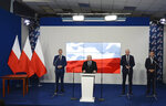 The leader of the Polish ruling party, Jaroslaw Kaczynski,center, speaks to reporters alongside Prime Minister Mateusz Morawiecki,left, and the leaders of two junior coalition partners, Jaroslw Gowin and Zbigniew Ziobro,right, in Warsaw, Poland, Saturday, Sept. 26, 2020. The three parties in Poland's conservative coalition government signed a new coalition agreement on Saturday, putting aside disagreements. But they gave no details, leaving lingering uncertainty about how the Cabinet will look in practice after an expected reshuffle.(AP Photo/Czarek Sokolowski)