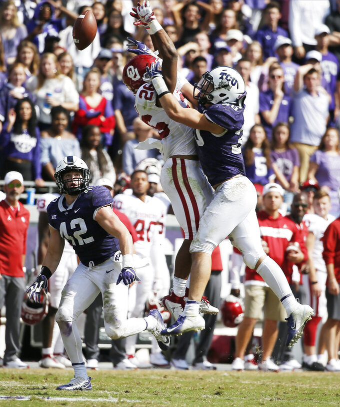 Oklahoma running back Kennedy Brooks is unable to catch a pass as TCU linebackers Garret Wallow (30) and Ty Summers (42) defend during the second half of an NCAA college football game, Saturday, Oct. 20, 2018, in Fort Worth, Texas. Oklahoma won 52-27. (AP Photo/Brandon Wade)