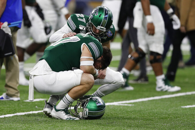 Eastern Michigan long snapper Drake Sutton (47) is consoled by punter Vinnie Patteri (27) after losing to Pittsburgh 34-30 in the Quick Lane Bowl NCAA college football game, Thursday, Dec. 26, 2019, in Detroit. (AP Photo/Carlos Osorio)
