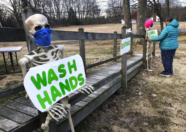 Belinda Brewer uses decorative skeletons to hold messages reminding the public of proper coronavirus preventative measures, outside her home, Wednesday, April 1, 2020, in Freeport, Maine. Gov. Janet Mills announced a statewide stay-at-home order starting Thursday in an attempt to limit the spread of coronavirus in the state.(AP Photo/Robert F. Bukaty)