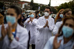 Healthcare workers protest against plans by Madrid's authorities to force staff to transfer to other hospitals at La Paz hospital in Madrid, Spain, Friday, Jan. 22, 2021. Virus infections have been increasing steeply following Christmas and New Year, putting pressure on Spain's public health system. (AP Photo/Manu Fernandez)