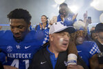 FILE - In this Sept. 22, 2018, file photo, Kentucky coach Mark Stoops celebrates with players and fans on the field after the team's 28-7 win over Mississippi State in an NCAA college football game, in Lexington, Ky. While at least one coach has been fired already in each of the other Power Five conferences, the SEC doesn't have anyone on an obvious hot seat heading into the final weekend of the regular season. Barring a surprise move, 2019 would mark the first time since 2006 that the SEC begins a season with no new head coaches. (AP Photo/Bryan Woolston, File)