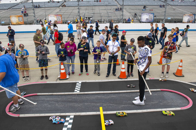 NASCAR fans race remote cars before the Drydene 400 - Monster Energy NASCAR Cup Series playoff auto race, Sunday, Oct. 6, 2019, at Dover International Speedway in Dover, Del. (AP Photo/Jason Minto)