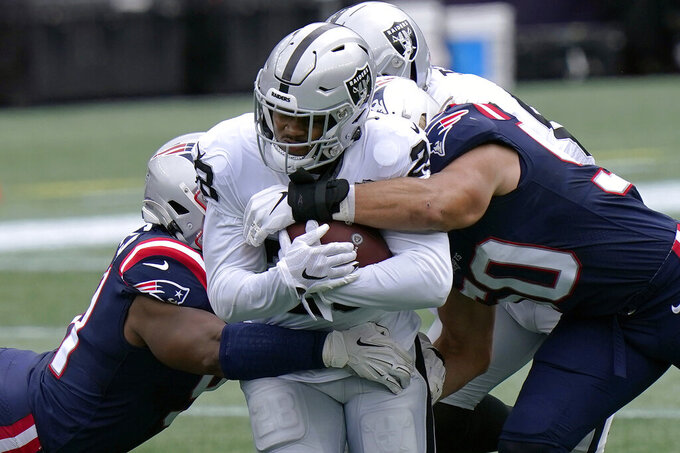 Las Vegas Raiders running back Josh Jacobs, center, runs with the ball against the New England Patriots in the first half of an NFL football game, Sunday, Sept. 27, 2020, in Foxborough, Mass. (AP Photo/Steven Senne)