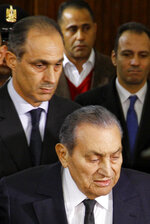 Former Egyptian President Hosni Mubarak arrives with with his son, Alaa, left, to testify in a courtroom at the national police academy in Cairo, Egypt, Wednesday, Dec. 26, 2018. Two former Egyptian presidents appeared Wednesday in the same Cairo courtroom, with Mubarak testifying in a retrial of Mohammed Morsi on charges related to prison breaks at the height of the 2011 uprising that toppled Mubarak. (AP Photo/Ahmed Abdel Fattah)