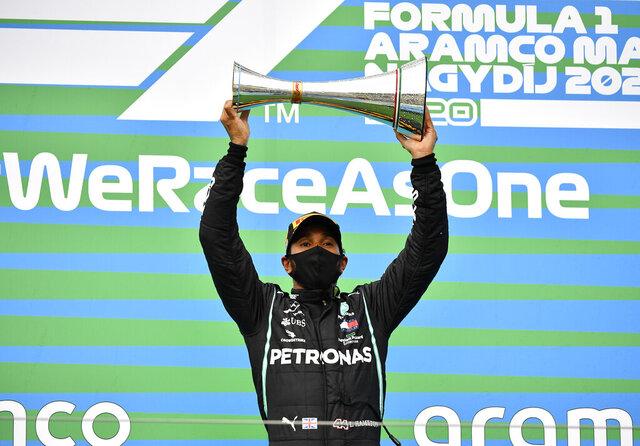 Mercedes driver Lewis Hamilton of Britain celebrates on the podium after winning the Hungarian Formula One Grand Prix at the Hungaroring racetrack in Mogyorod, Hungary, Sunday, July 19, 2020. (Joe Klamar/Pool via AP)
