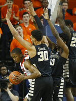 Virginia forward Mamadi Diakite (25) looks to pass as Wake Forest center Olivier Sarr (30), forward Jaylen Hoard (10) and guard Chaundee Brown (23) defend during the first half of an NCAA college basketball game in Charlottesville, Va., Tuesday, Jan. 22, 2019. (AP Photo/Steve Helber)