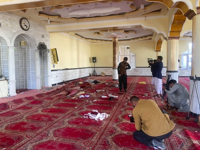 Afghan journalist take photos and film inside a mosque after a bomb explosion in Shakar Dara district of Kabul, Afghanistan, Friday, May 14, 2021. A bomb ripped through a mosque in northern Kabul during Friday prayers killing 12 worshippers, Afghan police said. (AP Photo/Rahmat Gul)