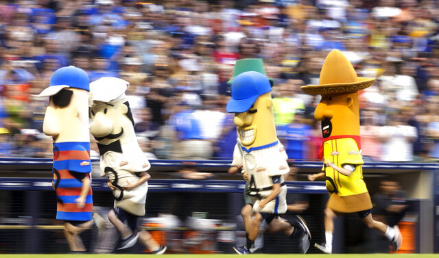 FILE - In this July 13, 2019, file photo, fans watch the racing sausages during a baseball game between the Milwaukee Brewers and the San Francisco Giants in Milwaukee. The chairman of the Wisconsin Republican Party, Andrew Hitt, is warning Milwaukee's chief elections official that it would be illegal for any Milwaukee Bucks or Brewers players or mascots to participate in early voting events planned at their stadiums in the days leading up to the election. Milwaukee plans to allow for in-person absentee voting at Miller Park and Fiserv Forum between Oct. 20 and Nov. 1.  (AP Photo/Morry Gash, File)