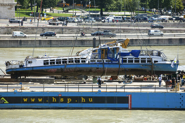 FILE- In this Tuesday, June 11, 2019, file photo a crane places the wreckage of the sightseeing boat on a transporting barge at Margaret Bridge, the scene of the fatal boat accident in Budapest, Hungary. Preparations are underway for commemorations to be held on the first anniversary of the May 29, 2019, mishap on the Danube River in which a sightseeing boat carrying mostly tourists from South Korea sank after a collision with a river cruise ship. Just seven of the 33 South Korean tourists aboard the Hableany (Mermaid) survived the nighttime collision.(Balazs Mohai/MTI via AP)