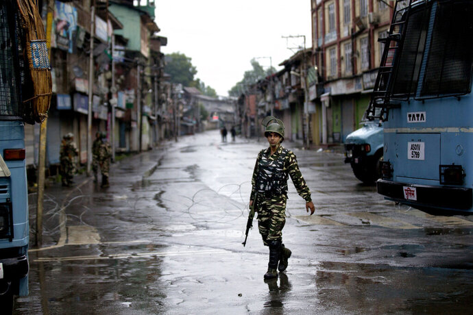 FILE - In this Aug. 14, 2019, file photo, an Indian paramilitary soldier patrols during a security lockdown after the Indian government stripped the Himalayan state's semi-autonomous powers in Srinagar, Indian controlled Kashmir. A year after India ended disputed Kashmir's semi-autonomous status and downgraded it to a federally governed territory, authorities have begun issuing residency and land ownership rights to outsiders for the first time in almost a century. Many Kashmiris view the move as the beginning of settler colonialism aimed at engineering a demographic change in India's only Muslim-majority region. (AP Photo/ Dar Yasin, File)
