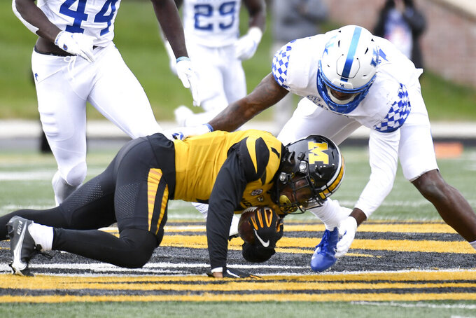 Missouri running back Tyler Badie, left, struggles for yardage before being stopped by Kentucky linebacker J.J. Weaver during the first half of an NCAA college football game Saturday, Oct. 24, 2020, in Columbia, Mo. (AP Photo/L.G. Patterson)