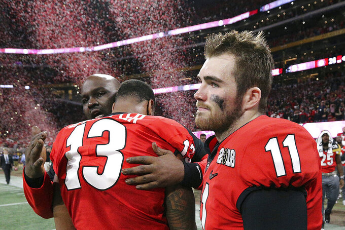 """FILE- In this Jan. 8, 2018, file photo, Georgia's Jake Fromm and Jonathan Ledbetter reacts after their overtime lose to Alabama in College Football Playoff National Championship game in Atlanta. As the World Series comes to Atlanta for the first time since 1999, there is hope that the city — once immortalized by Sports Illustrated as """"Loserville"""" — and the entire state of Georgia, for that matter, could be taking a turn toward some long-overdue parades and celebrations.  (Curtis Compton/Atlanta Journal-Constitution via AP, File)"""