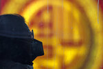 A commuter wearing a mask rides on a bus passing by a prosperity sign in Beijing, Sunday, Feb. 9, 2020. China's virus death toll on Sunday have surpassed the number of fatalities in the 2002-2003 SARS epidemic, but fewer new cases were reported in a possible sign its spread may be slowing as other nations step up efforts to block the disease. (AP Photo/Andy Wong)