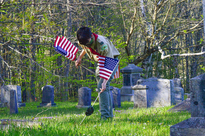 Jack Mosher, a member of Boy Scouts Troop 461, puts an American flag on to veteran gravesites at West Dover Village Cemetery in Dover, Vt., Thursday, May 21, 2020, in observance of Memorial Day. (Kristopher Radder/The Brattleboro Reformer via AP)