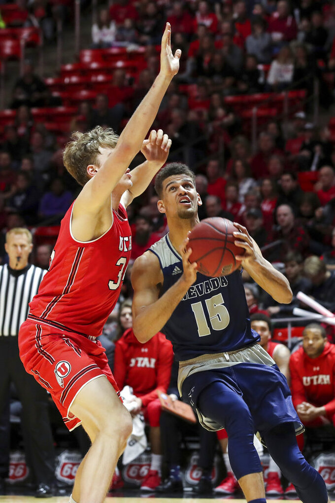 Nevada forward Trey Porter (15) looks to shoot the ball past Utah center Jayce Johnson (34) during the first half of an NCAA college basketball game, Saturday, Dec. 29, 2018, in Salt Lake City. (AP Photo/Chris Nicoll)