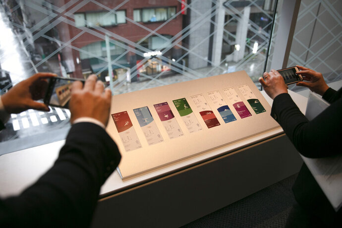 People photograph tickets for the Tokyo 2020 Olympics and Paralympics Wednesday, Jan. 15, 2020, in Tokyo. (AP Photo/Jae C. Hong)