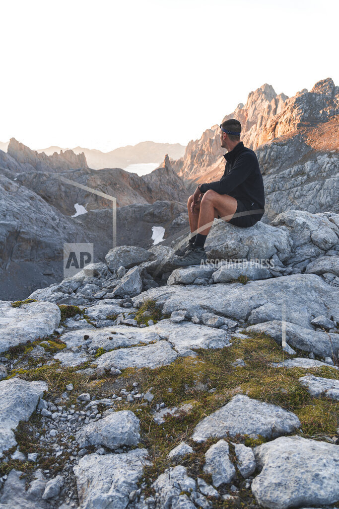 Young man sitting on rock at Picos de Europe mountain range, Cantabria, Spain