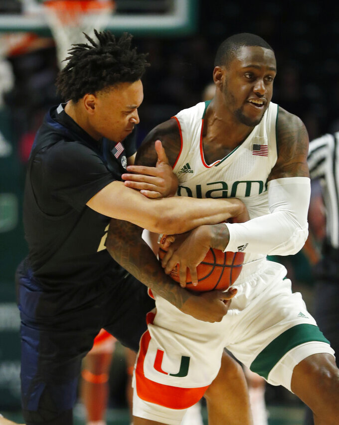Pittsburgh guard Trey McGowens, left, and Miami guard Zach Johnson, right, battle for a ball during the first half of an NCAA college basketball game, Tuesday, March 5, 2019, in Coral Gables, Fla. (AP Photo/Wilfredo Lee)