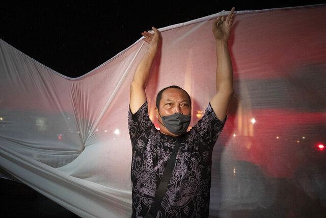 An anti-government activist tries to set up a shite sheet to project a video in Bangkok, Thailand, Wednesday, June 24, 2020. Anti-government activists in the Thai capital Bangkok on Wednesday held a pre-dawn commemoration of a military coup that installed constitutional rule almost nine decades ago, defying official warnings and police harassment. (AP Photo/Sakchai Lalit)