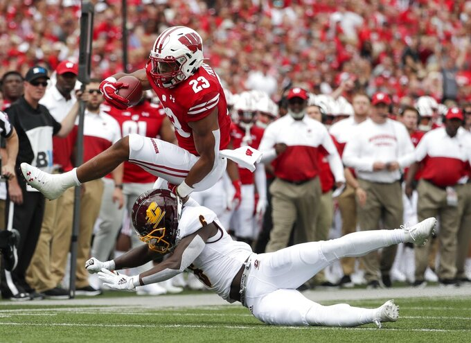 Wisconsin's Jonathan Taylor tries to leap over Central Michigan's Da'Quaun Jamison during the first half of an NCAA college football game Saturday, Sept. 7, 2019, in Madison, Wis. (AP Photo/Morry Gash)