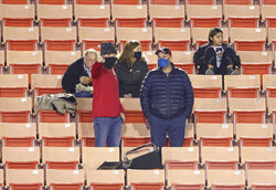 Fans attending the NCAA college football game between Northern Illinois and Buffalo on Wednesday night, Nov. 4, 2020, in DeKalb, Ill., follow guidelines about mask-wearing and social distancing. (Mark Busch/Daily Chronicle via AP)