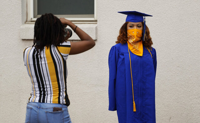 Anderson High School senior Teyaja Jones, right, poses in her cap and gown and a bandana face cover, Tuesday, May 5, 2020, in Austin, Texas. Texas' stay-at-home orders due to the COVID-19 pandemic have expired and Texas Gov. Greg Abbott has eased restrictions on many businesses that have now opened, but school buildings remain closed. (AP Photo/Eric Gay)