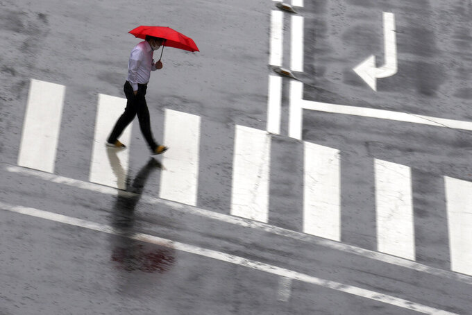 A man wearing a protective mask to help curb the spread of the coronavirus walks along a pedestrian crossing in a sudden rain Thursday, June 17, 2021, in Tokyo. (AP Photo/Eugene Hoshiko)
