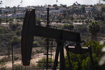 Homes are seen behind pump jacks operating at the Inglewood Oil Field in Los Angeles, Tuesday, May 18, 2021. California Gov. Gavin Newsom has set some of the nation's most ambitious goals for weaning his state off oil, including a ban on the sale of new gas-powered cars by 2035 and the end of oil production a decade later. (AP Photo/Jae C. Hong)