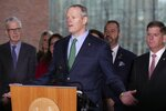 Massachusetts Gov. Charlie Baker, center, speaks during a news conference outside Boston City Hall in front of Mayor Marty Walsh, right, and CEO of the Boston Athletic Association Thomas Grilk, left, Friday, March, 13, 2020, in Boston, where it was announced that the Boston Marathon, which was due to be run on April 20, will be postponed until Monday, Sept.14, 2020, due to concerns about the coronavirus. For most people, the new coronavirus causes only mild or moderate symptoms, such as fever and cough. For some, especially older adults and people with existing health problems, it can cause more severe illness, including pneumonia. The vast majority of people recover from the new virus. (AP Photo/Michael Dwyer)
