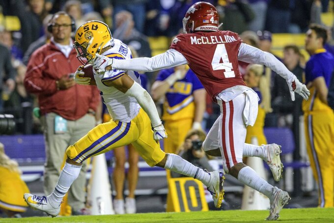 LSU running back John Emery Jr. (4) runs for a touchdown as Arkansas defensive back Jarques McClellion (4) pursues during the second half of an NCAA college football game in Baton Rouge, La., Saturday, Nov. 23, 2019. (AP Photo/Matthew Hinton)