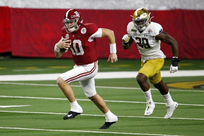 Alabama quarterback Mac Jones (10) runs the ball as Notre Dame defensive lineman Ovie Oghoufo (29) gives chase in the first half of the Rose Bowl NCAA college football game in Arlington, Texas, Friday, Jan. 1, 2021. (AP Photo/Roger Steinman)