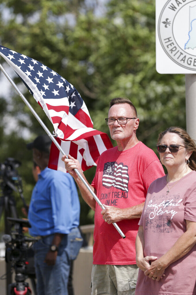 """Jeff DuBois holds an American flag as the funeral procession for Marine Cpl. Humberto """"Bert"""" Sanchez passes by, Tuesday, Sept. 14, 2021, in Logansport, Ind. Sanchez was one of 13 U.S. service members to die in an explosion during evacuation efforts in Afghanistan. (Nikos Frazier/Journal & Courier via AP)"""