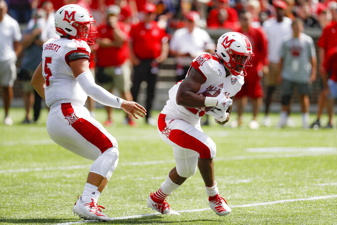 Miami of Ohio running back Tyre Shelton, right, takes a hand off from quarterback Brett Gabbert (5) before scoring a touchdown in the first half of an NCAA college football game against Cincinnati, Saturday, Sept. 14, 2019, in Cincinnati. (AP Photo/John Minchillo)
