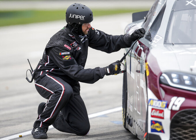 A member of Brandon Jones' pit crew makes repairs to his car during a NASCAR auto race at Texas Motor Speedway, Saturday, March 30, 2019, in Fort Worth, Texas. (AP Photo/Brandon Wade)